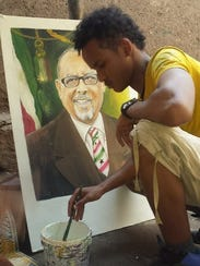 Abdulfatah paints a portrait. He is one of a family
