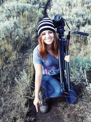 Angel Amaya poses with a wolf print at Yellowstone