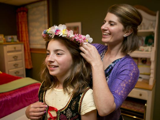 Sabrina Erdman places the crown of flowers on her daughter Lily's head Wednesday at their home in the town of Rose. Lily Erdman is the Miss United States Polka Association Polka Princess.
