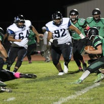 Quarterback Hogan Fowles looks for running room in Friday night's game.