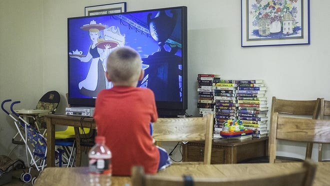 A kid watches a movie at A Better Way domestic violence shelter.