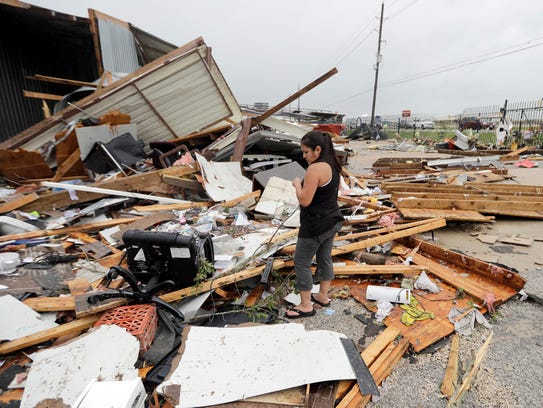 Jennifer Bryant looks over the debris from her family