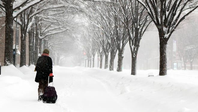 Michelle Navarre Cleary pulls a bag as she walks on K Street in Washington on Jan. 23, 2016, as snow continues to fall.