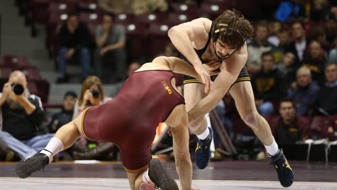Iowa's Mike Evans avoids being taken down by Minnesota's Logan Storley in the 174 pound weight class of an NCAA wrestling match Friday, Jan. 30, 2015 in Minneapolis.