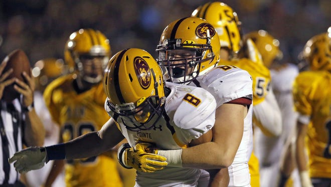 Mountain Pointe running back Macarius Blount celebrates a touchdown with teammate Coleton Waller, #81, during the 4th quarter of a high school football game at Marcos de Niza in Tempe on Friday, August 21, 2015.