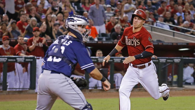Arizona Diamondbacks' Jake Lamb (19) scores behind San Diego Padres catcher Austin Hedges (18) on a two-run RBI single by Chris Owings in the 4th inning of their MLB game Wednesday, Sept. 16, 2015 in Phoenix, Ariz.