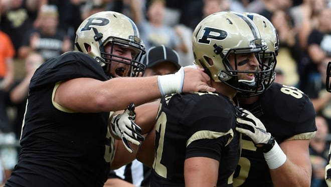Purdue Boilermakers quarterback Austin Appleby (12) is congratulated by his teammates after a touchdown in the first half at Ross Ade Stadium.