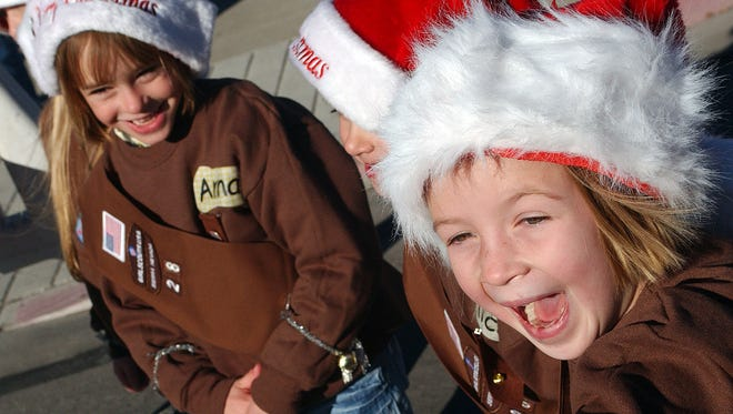 Anna, left, and Alice Benedict and Emma Jerz of Reno/Sparks Brownie Troop 28 watch the parade during the 2005 Sparks Hometowne Christmas.