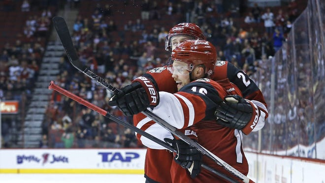 Oliver Ekman-Larsson and Max Domi (front) celebrate a Domi goal Tuesday against the Oilers.