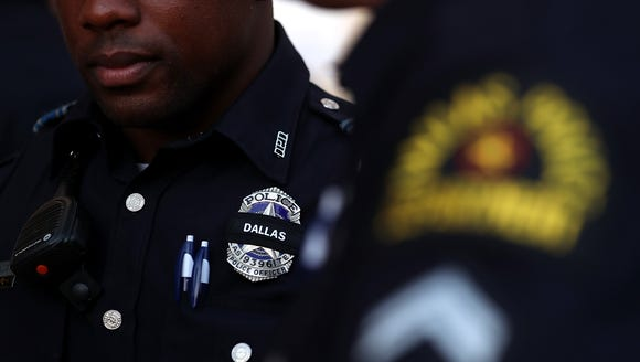 A Dallas police officer wears a black band on his badge