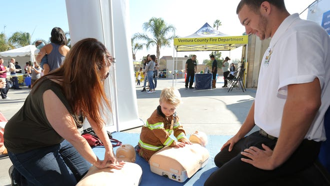 Ventura College EMT student Kody Poe, right, shows Tina Shoemaker and her son Gabriel Biondo, 2, how to administer CPR during a pancake breakfast at Ventura County Fire Station No. 41 in Simi Valley on Saturday. The department was also promoting a smart phone app that alerts users of calls for cardiac arrests.