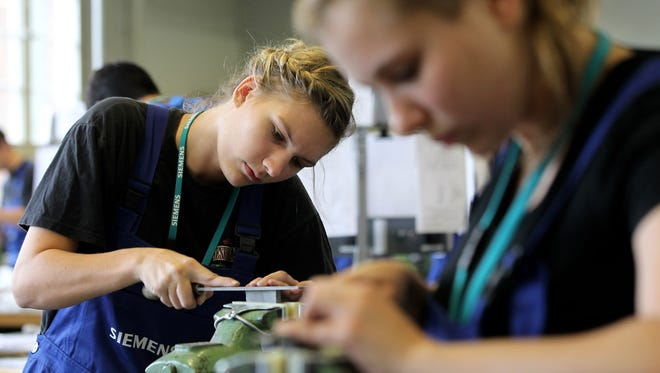 Female mechanical engineering trainees learn the basics of precision filing at the Siemens training center on in Berlin, Germany. Approximately 320 trainees are beginning this year's program at Siemens, which is a dual program that offers a Bachelor's degree as well as hands-on work training.