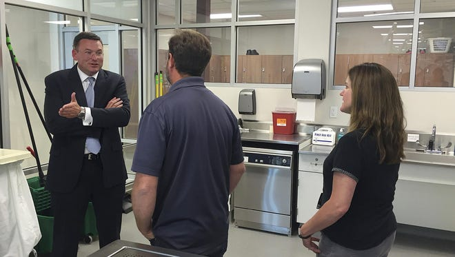 Dr. Robert Hasty, the dean of the for-profit Idaho College of Osteopathic Medicine, talks with Idaho State University Meridian Health Science Center employees Chris Wilson, center, and Nancy Carpenter at the facility in Meridian, Idaho, on June 20.