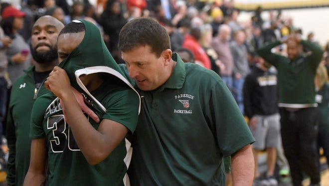 Parkside head coach David Byer, center, consoles Paul Morgan after the team's 59-57 loss to Harford Tech in the Maryland Class 2A East high school basketball regional final in Bel Air.