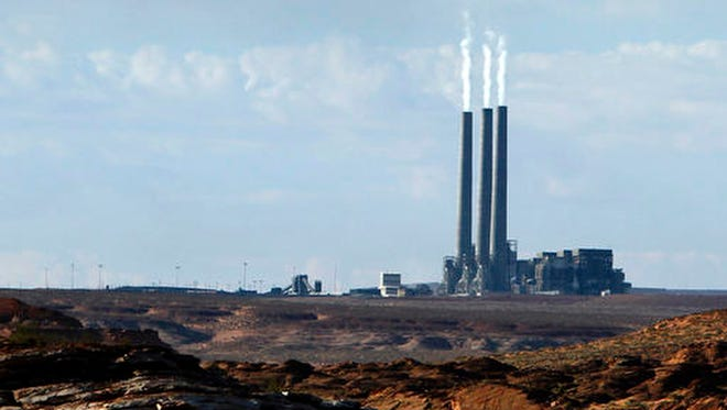 In this Sept. 4, 2011 photo, smoke rises from the stacks of the main plant facility at the Navajo Generating Station, as seen from Lake Powell in Page, Ariz. Navajo Nation officials and the power utility that is the Navajo Generating Station's managing owner are expressing optimism about reaching an agreement soon to keep the coal-fired plant operating through 2019.