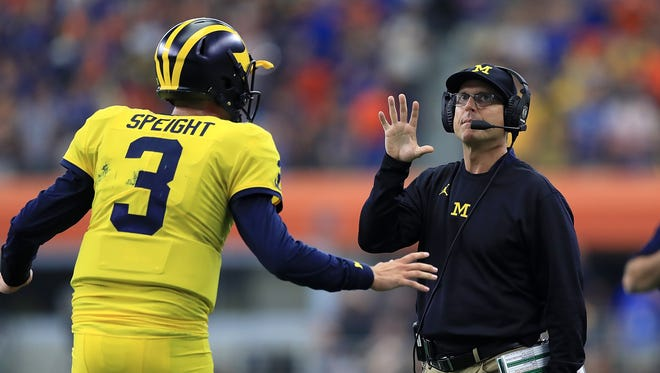 Michigan quarterback Wilton Speight talks with head coach Jim Harbaugh in the first quarter against Florida at AT&T Stadium on Sept. 2, 2017 in Arlington, Texas.