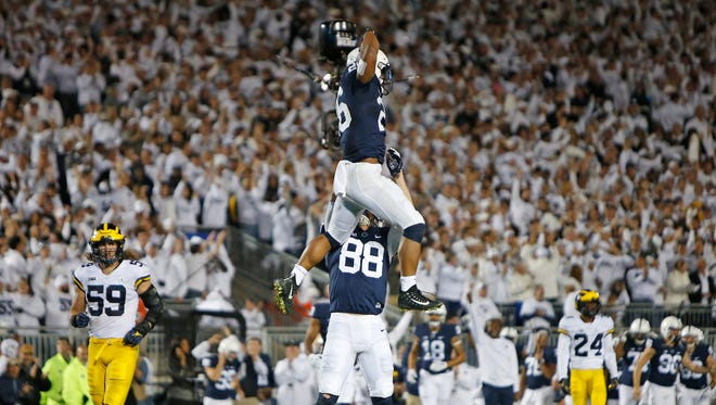 Penn State's Saquon Barkley, top, celebrates after catching a 42-yard touchdown pass in the second half against Michigan on Oct. 21, 2017 at Beaver Stadium in University Park, Pa.