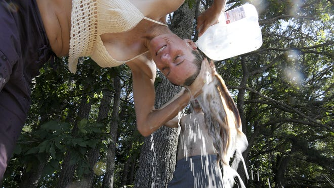 Patricia and Roger Clark wash their hair using bottled water at the campgrounds at the Bonnaroo Music & Arts Festival in Manchester, Tenn., on Friday, June 9, 2017.