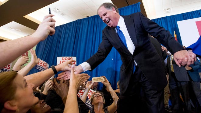Doug Jones greets supporters as he claims victory at his watch party in Birmingham.