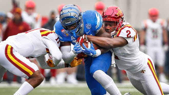 Memphis running back Patrick Taylor Jr., (middle) fights for positive yards against Iowa State defenders Lawrence White (left) and Willie Harvey (right) during third quarter action of the AutoZone Liberty Bowl in Memphis, Tenn., Saturday, December 30, 2017.
