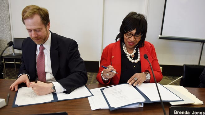 David Nicholson and Council president Brenda Jones, sign the official documents that release the city from financial oversight.