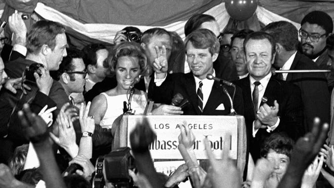 Sen. Robert F. Kennedy speaks his final words to supporters at the Ambassador Hotel in Los Angeles, moments before he was shot on June 5, 1968. At his side are his wife, Ethel, left, and his California campaign manager, Jesse Unruh, right. Football player Roosevelt Grier is at right rear.