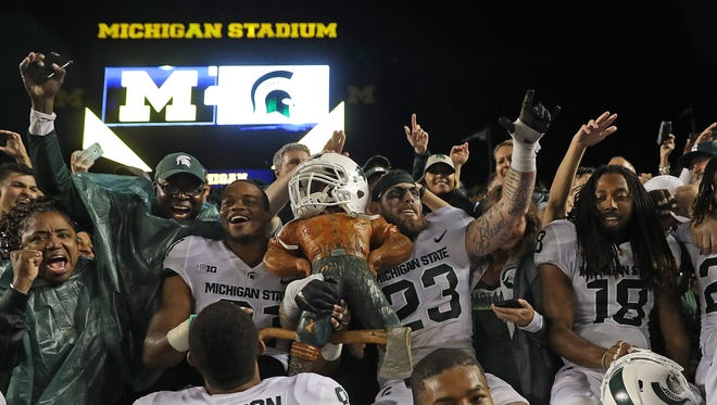 Michigan State players celebrate with the Paul Bunyan Trophy after winning in Michigan Stadium last season.