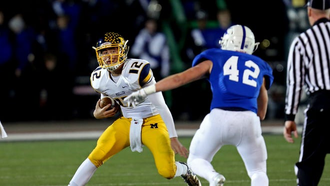 Moeller QB Matt Crable looks for room to run around St. Xavier linebacker Elijah Payne.