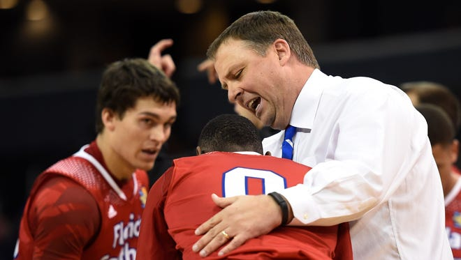 Florida Southern coach Linc Darner checks on Kevin Capers while Dylan Travis watches during the second half against Indiana (Pa.) in the NCAA Division II championship game March 28 in Evansville, Ind.