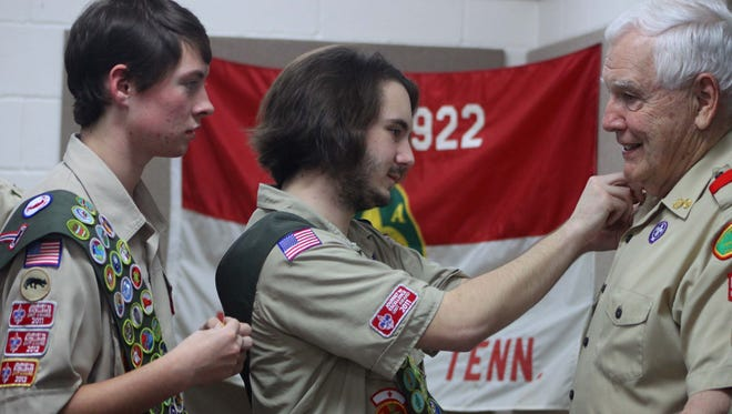 Dylan Vaughan attaches a mentor pin to Durward Baxter during an Eagle Scout ceremony at the Middleton Community Center on Saturday.
