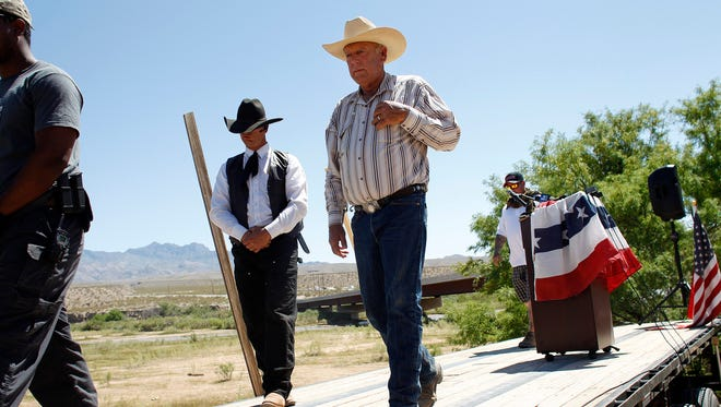 Rancher Cliven Bundy (center) walks off stage after speaking at a news conference near Bunkerville, Nev., Thursday, April 24, 2014. Bundy, a Nevada rancher who became a conservative folk hero for standing up to the government in a fight over grazing rights, lost some of his staunch defenders after wondering aloud whether blacks might have had it better under slavery.
