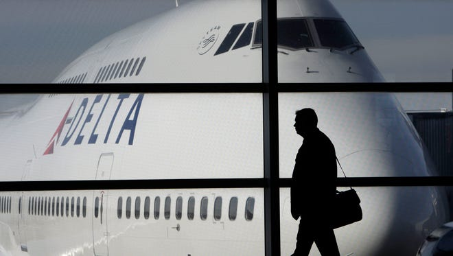In this file photo from Jan. 21, 2010, a passenger walks past a Delta Air Lines Boeing 747 at Detroit Metropolitan Wayne County Airport.