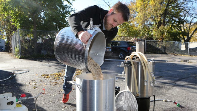 "Derek Boyce from Mamaroneck pours grain into a pot of heated water during the ""Teach a Friend to Homebrew Day"" at the Westchester Homebrew Emporium in New Rochelle, Nov. 5, 2016."