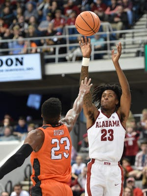 Alabama's John Petty (23) shoots for three over Mercer's Demetre Rivers (23) in an NCAA college basketball game in Huntsville, Ala., Tuesday, Dec. 19, 2017. Alabama won, 80-79.
