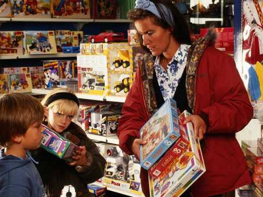 A woman shops with two children in a toy store.