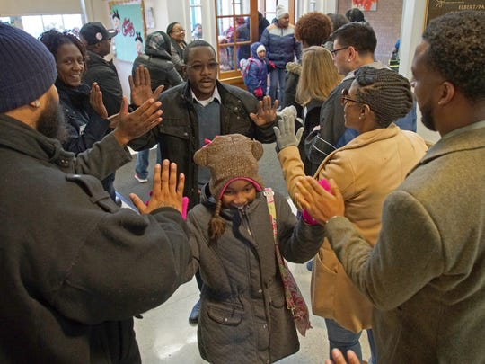 """Tim Coward and his 10 year-old daughter Kiasia a third grader at Elbert-Palmer Elementary are greeted by volunteers, school staff and fellow fathers Monday morning on """"Bring Your Dad to School Day,""""  hosted by the Fathership Foundation."""