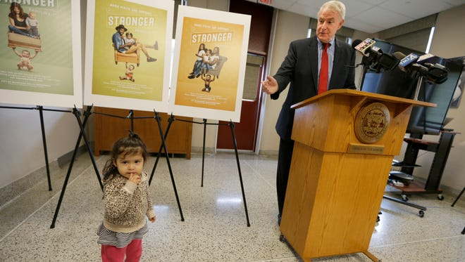 Milwaukee Mayor Tom Barrett talks about the Strong Baby advertising campaign during a news conference as toddler Ariadne Gomez-Valenciano  stands near the campaign's promotional posters. The campaign encourages families to participate in one of the city's most successful efforts, the Health Department's nurse visiting program for expecting mothers.