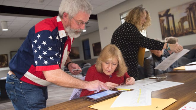 Steve and Denise Smith work to sign voters in before a GOP caucus at Loveland Classical Schools on W. 29th Street in Loveland on Tuesday, March 6, 2018.