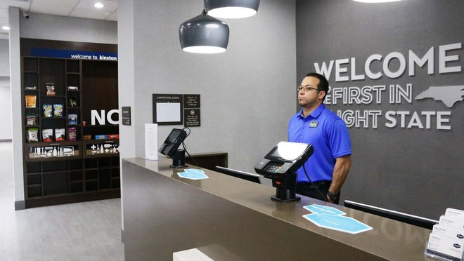 Hampton Inn assistant general manager Jayson Melendez stands behind the hotel's desk in May and looks at an empty lobby amid the coronavirus pandemic.