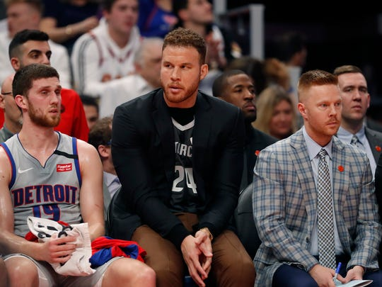 Detroit Pistons forward Blake Griffin, wearing a jersey in tribute to Kobe Bryant sits with guard Sviatoslav Mykhailiuk (19) and assistant coach Sean Sweeney during the first half of an NBA basketball game against the Cleveland Cavaliers, Monday, Jan. 27, 2020, in Detroit. (AP Photo/Carlos Osorio)