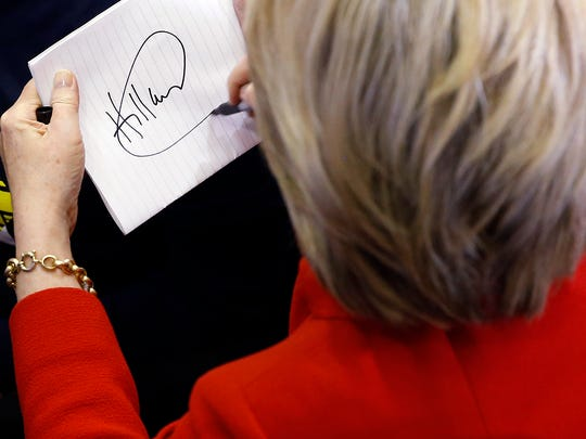 Democratic presidential candidate Hillary Clinton signs