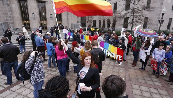 Amanda Keller holds a flag as she joins other gay marriage supporters in Linn Park at the Jefferson County courthouse in Birmingham, Ala., on Feb. 9, 2015.