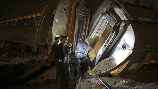 Emergency personnel respond to the wreck of an Amtrak train in Philadelphia on May 12, 2015. Amtrak says it will install video cameras inside locomotive cabs to record the actions of train engineers.