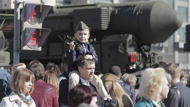 People walk along as a Russian strategic ballistic missile RS-24 Yars launching vehicle participates in the rehearsal for the Victory Day military parade in Moscow in May 2015.