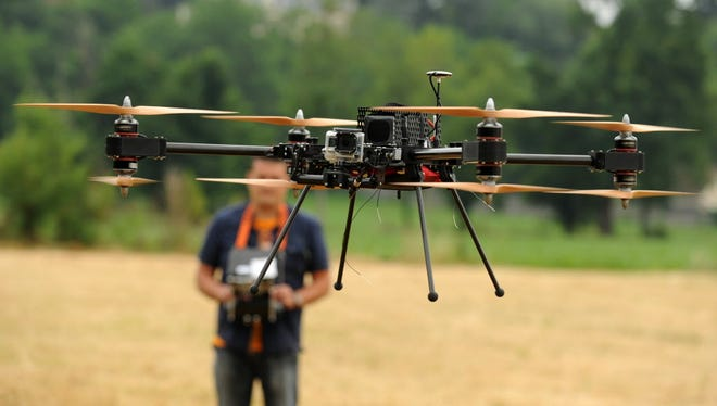 A man operates with a remote control a 4-8X Dual Atex drone on June 6, 2015 in Pau, southwestern France.