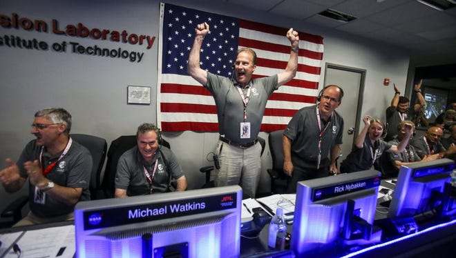 From left to right, Geoffrey Yoder, Michael Watkins, Rick Nybakken, Richard Cook and Jan Chodas celebrate in Mission Control at NASA's Jet Propulsion Laboratory as the solar-powered Juno spacecraft goes into orbit around Jupiter on Monday in Pasadena, Calif.