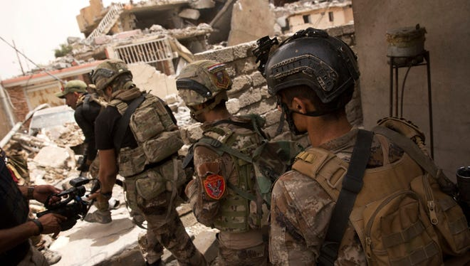 In this May 11, file photo Iraqi special forces advance to their next position in the Islah al-Zarai area in Mosul, Iraq. U.S.-backed Iraqi forces were moving to surround Mosul's Old City after launching a fresh push to drive Islamic State militants from areas they still hold.