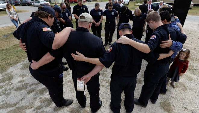 First responders in Sutherland Springs, Texas, pray after a Veterans Day event on Nov. 11, 2017, near the First Baptist Church where a gunman killed 25 people including a pregnant woman.