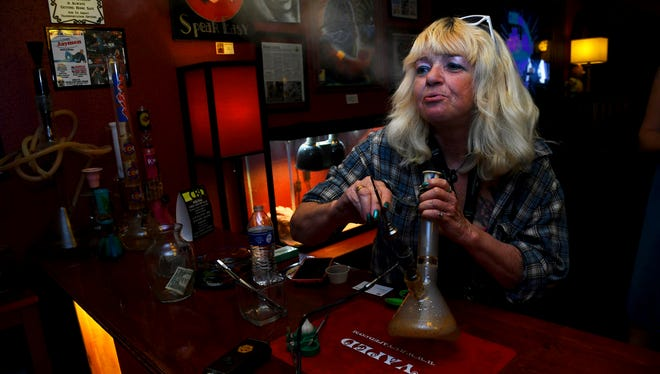 "In this April, 12, 2017 file photo, Linda Wood smokes a concentrated form of marijuana called a ""dab"" at the Speakeasy Vape Lounge, one of the United States' only legal pot clubs, in Colorado Springs, Colo. Industry advocates say Gov. John Hickenlooper's June 4, 2018 veto of a bill allowing tasting rooms inside marijuana retailers will ensure that clubs like Speakeasy continue to operate without state regulation."