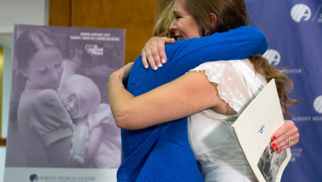 Nurse Susan Berger, left, and Amanda Scarpinati hug during a news conference at Albany Medical Center in New York, Scarpinati, who suffered severe burns as an infant, is finally getting the chance to thank Berger who cared for her, thanks to a social media posting that revealed the identity of the nurse in 38-year-old photos.